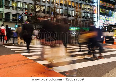TOKYO - MARCH 31, 2016: Pedestrians walk at Shinjuku Crossing. The Shinjuku Crossing is one of the busiest in the world and it is a famous tourist spot.