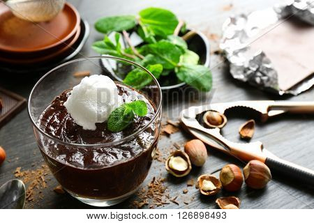 Glass cup of chocolate dessert with fresh mint and frothed milk on black wooden table