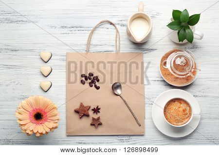 Cop of coffee and brown sugar on wooden table, top view