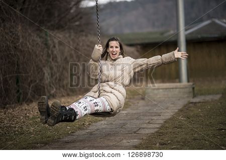Young woman enjoying life having fun outside in a park on a swing laughing with enjoyment as she flies through the air with one arm wide open.