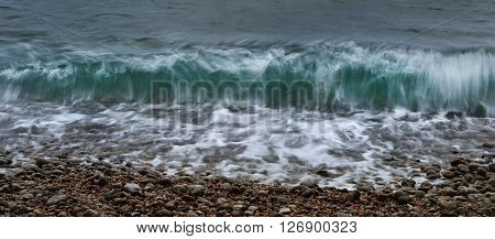 Green Ocean Waves Crashing Against Pebble Beach During Sunset