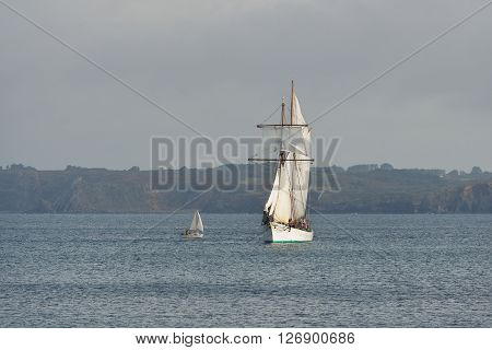 French Tall Ship With Full Sails And A Small Yacht At The Coast Of Brittany, France