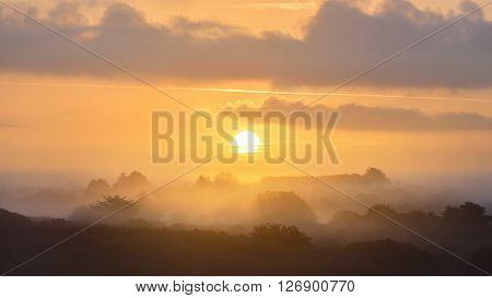 Golden Sunrise Over Misty Hills In Brittany, France