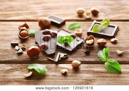 Chopped chocolate bar  with mint and hazelnuts on wooden table.