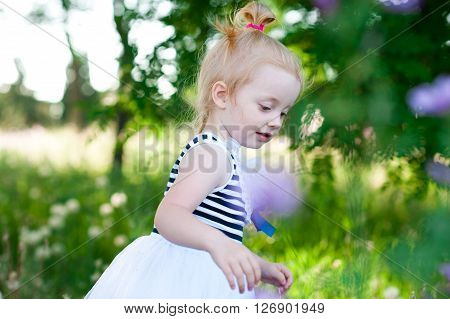 Cute baby girl 2-3 year old walking in park outdoors. Childhood.