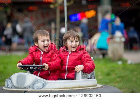 Two boys riding boat in amusement park having fun