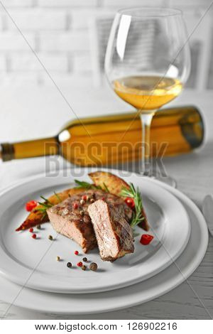 Delicious grilled steak on plate with white wine