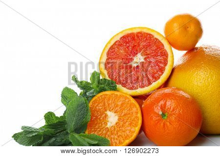 A heap of mixed citrus fruit sliced and unpeeled with mint sprigs isolated on a white background, close up