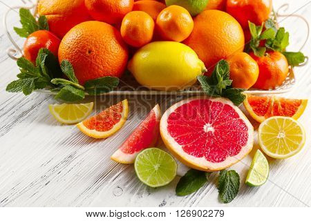 Set of different citrus fruit on light wooden background
