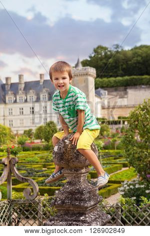 Cute Child, Sitting On A Stone Fence In Front Of The Villandry Castle On Loire