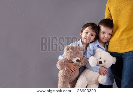 Happy Little Children, Boys, Hugging Their Mother At Home, Isolated Image, Copy Space. Family Concep
