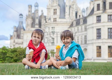 Two adorable boys in casual clothing eating ice cream sitting on a lawn in front of the biggest castle along the Loire river Chambord on sunset castle magnificiently arousing behind them