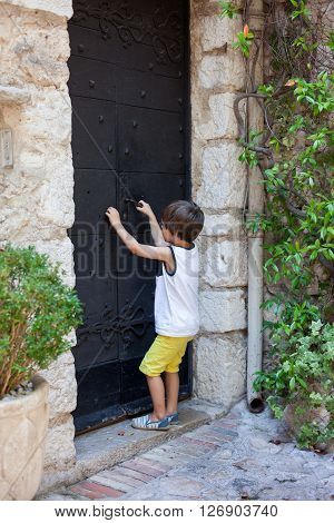 Little boy knocking on a old medieval door in an old village