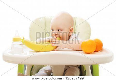 Baby Bites Banana Fruits At The Table Home
