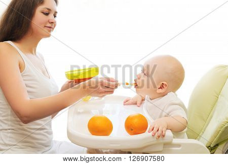 Mother Feeds Baby Spoon On Table At Home
