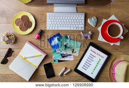 A flat lay image of a busy desk full of items needed to book a vacation including to do list, photographs and tea and biscuits.