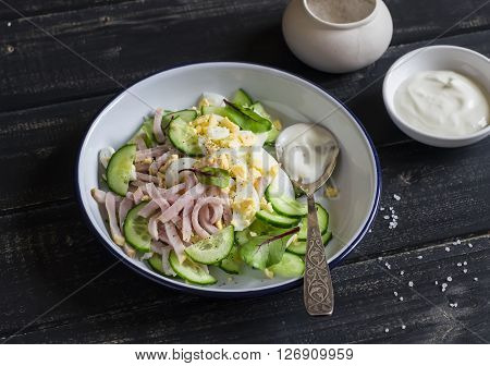 Easy and fast salad with smoked turkey cucumber and boiled egg on a dark wooden background. Healthy food
