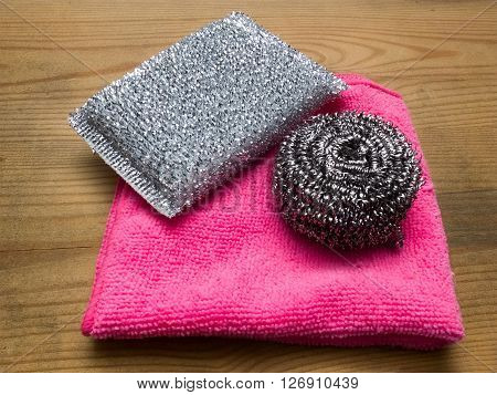 Microfiber cleaning cloth and metallic kitchen sponges on wooden background