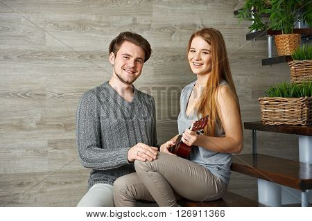Young girlfriend playing ukulele for her boyfriend on stairs