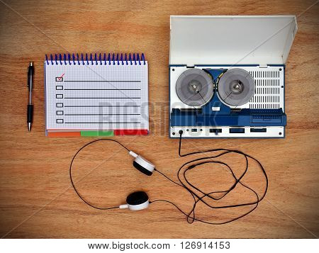 Reel tape recorder with headphones. Notepad with check box on wooden table. View from above