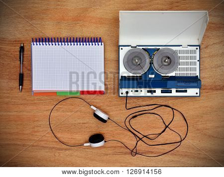 Reel tape recorder with headphones and blank notepad on wooden table. View from above