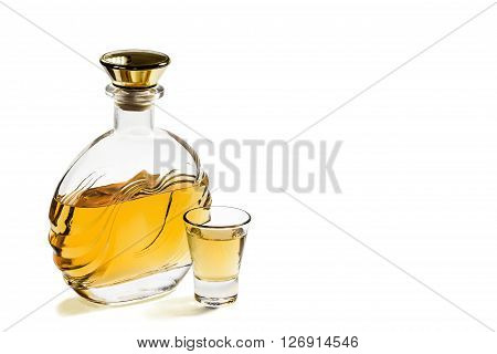 Bottle and a shot glass of tequila on a white background