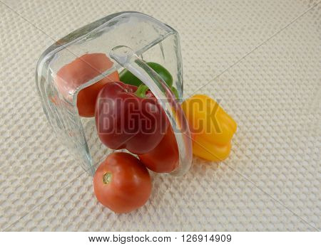 Peppers and tomatoes in overturned glass basket