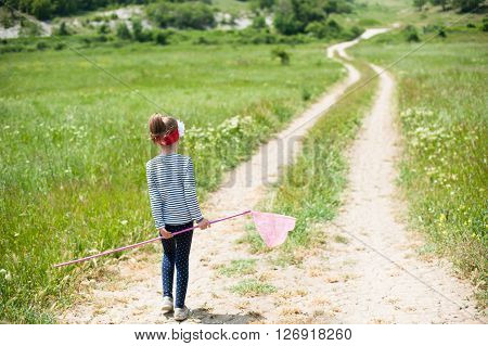 girl with a butterfly net is on the trail