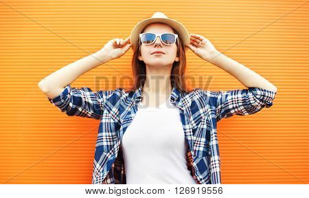 Fashion Woman Wearing A Straw Hat And Sunglasses Over Orange Background