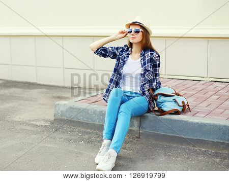 Pretty Young Woman Wearing A Sunglasses Summer Straw Hat And Checkered Shirt With Backpack In City