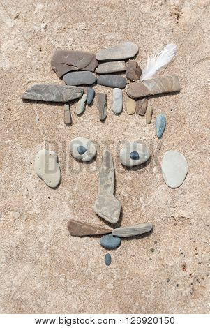 The man's face made out of stones on the sand, Indiana Dunes
