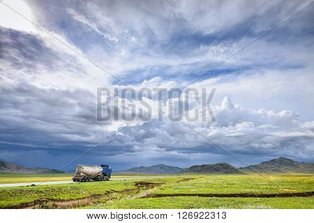 summer mountain and hazy sky landscape with truck on road
