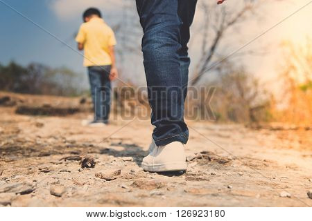 Two Boy Walking On The Rocky Land.