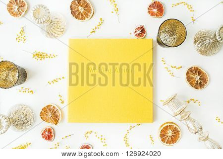yellow wedding photo album dry oranges candlesticks branches of mimosa isolated on white background. flat lay overhead view