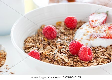 Homemade oat meal granola or muesli with fresh summer fruits - raspberry and strawberry with yogurt in a white bowl on a table for breakfast closeup selective focus