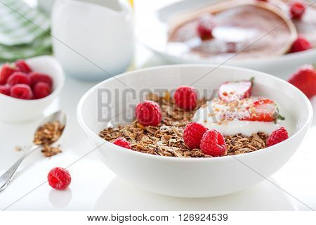 Homemade oat meal granola or muesli with fresh summer fruits - raspberry and strawberry with yogurt in a white bowl on a table for breakfast closeup