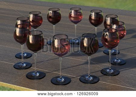 Tasting with circle palette of glasses with red and roze wine on the wooden table.
