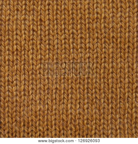 Pastel yellow wool knitted fabric texture. Close up fragment of the top view.