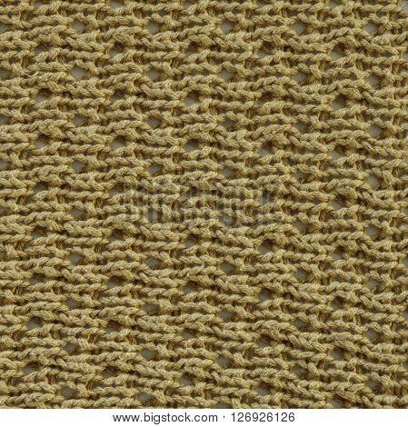 Pale yellow wool knitted fabric texture. Close up fragment of the top view.