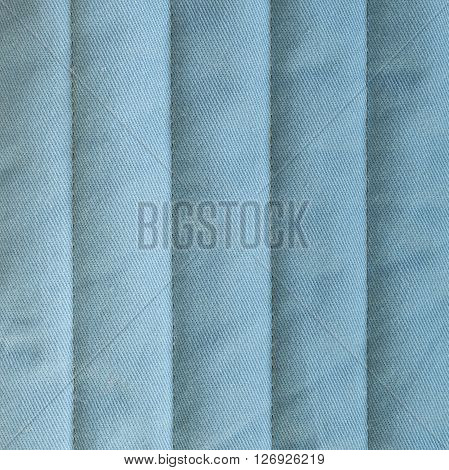 Pale blue textiles with insulation. Vertical stripes. Close up fragment of the top view.