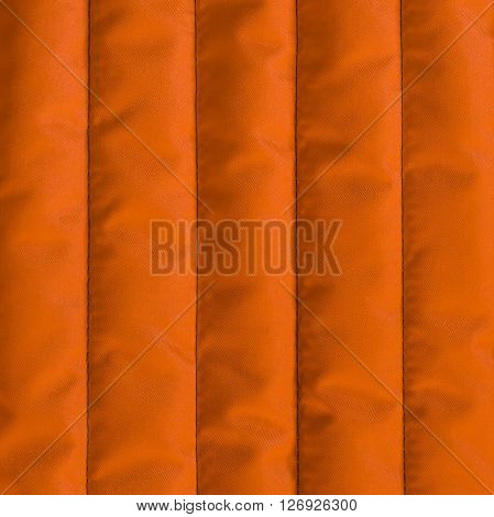 Orange quilted textiles with insulation. Vertical stripes. Close up fragment of the top view.