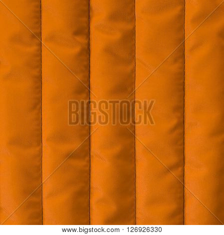 Orange yellow quilted textile with insulation texture. Vertical stripes. Close up fragment of the top view.