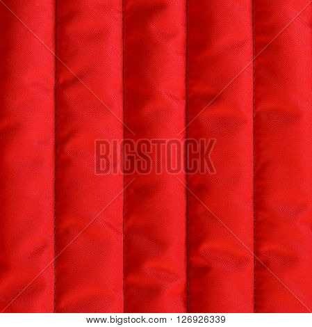Red quilted textiles with insulation texture. Vertical stripes. Close up fragment of the top view.