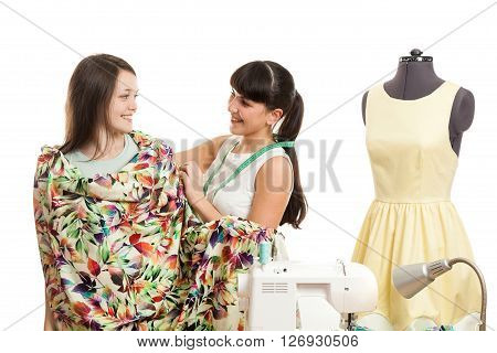 the seamstress tries on fabric on the girl the client
