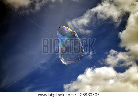 Soap rainbow bubble on blue sky background ** Note: Visible grain at 100%, best at smaller sizes