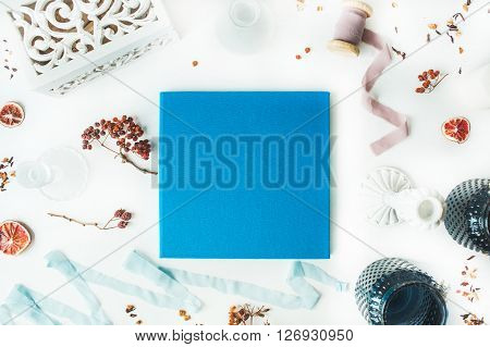 blue wedding or family photo album with stamped tree candlesticks blue ribbon dry oranges and rowan branches isolated on white background. flat lay overhead view