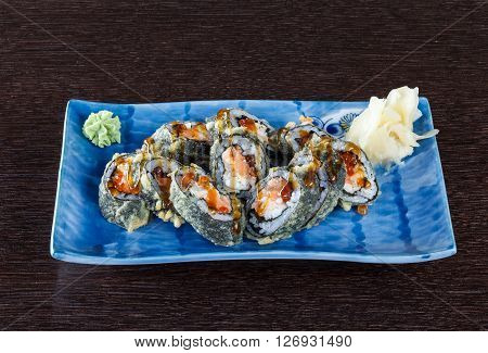 Sushi rolls on a plate with flying fish roe and tuna on dark brown wooden table. Side view.