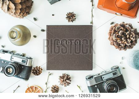 black wedding or family photo album cones vintage old-fashioned camera candlesticks branches of willow leaves and dry oranges isolated on white background. flat lay overhead view