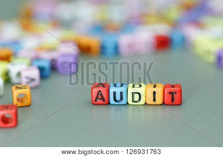 Close up of Audit word on colorful dices