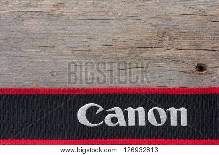 Kamennomostskiy Russia - 23 April 2016: the Canon Logo on the shoulder strap for the camera on old gray wooden background. with space for text
